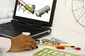 picture of mechanical drawing  - An engineer drafting engineering works with blank monitor - JPG