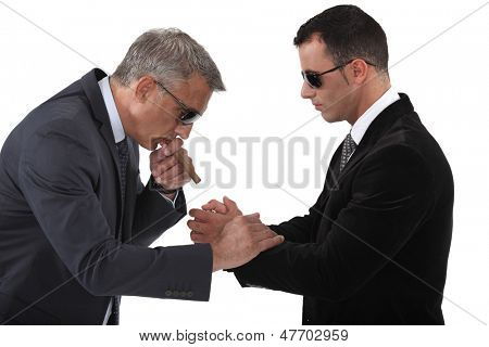 Mobster helping his boss light a cigar