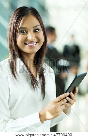 attractive indian office worker holding tablet computer in office