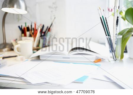 Artist's desk with books, papers and brushes