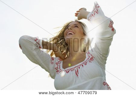 Low angle view of cheerful young woman on sunny day
