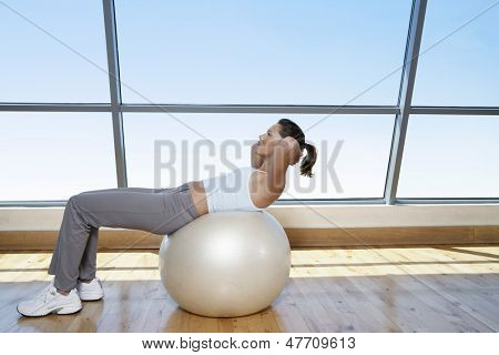 Side view of young fit woman doing sit-ups on exercise ball in gym