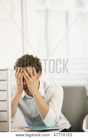 Stressed young male executive sitting in cubicle with head in hands
