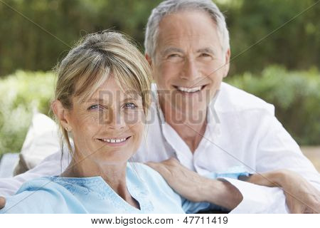 Portrait of happy middle aged couple relaxing in garden