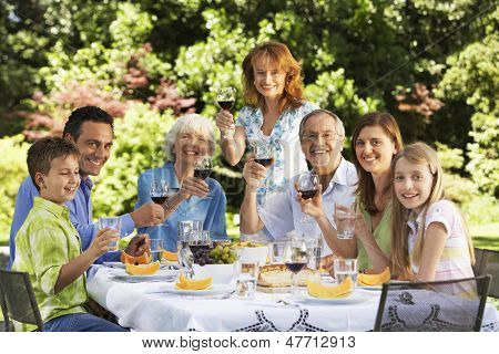 Portrait of happy family holding wine glasses at table in back yard