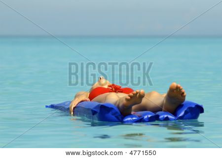 Woman Sunbathing On An Air Mattress