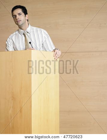 Young businessman talking at podium in conference room