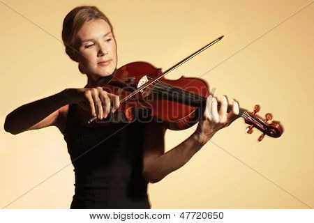 Young woman playing the violin against colored background