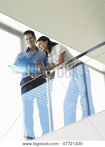 Low angle view of happy businessman with female colleague reviewing file in office lobby