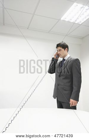 Serious young businessman using the landline phone