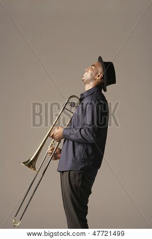 Side view of a happy African American man with trombone standing against brown background