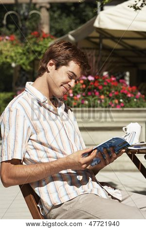 Young man reading guidebook at the outdoor cafe