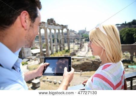 Couple of tourists using tablet by the Roman Forum