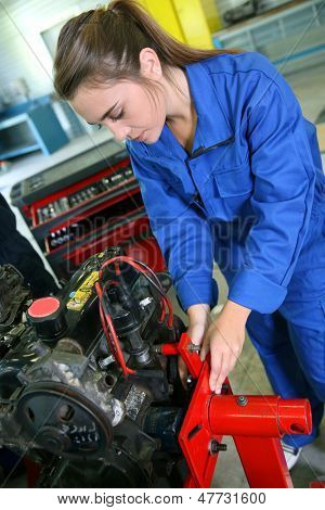Student girl working in auto repairshop
