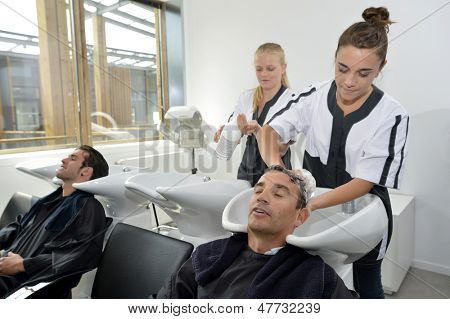 Young women in hairdress training washing customer's hair