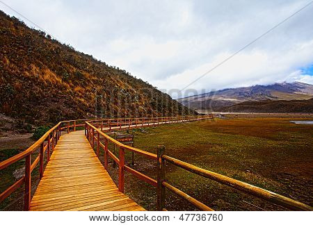 Wooden Bridge With A View On The Volcano Cotopaxi