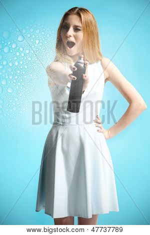 Beautiful girl in a white dress holding a bottle with hairspray