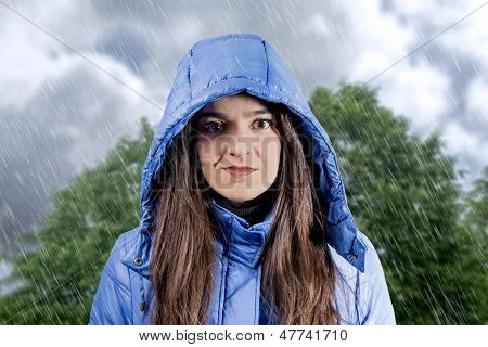 Portrait Of Beautiful Young Girl Wearing Aincoat With Hood In A Rainy Day