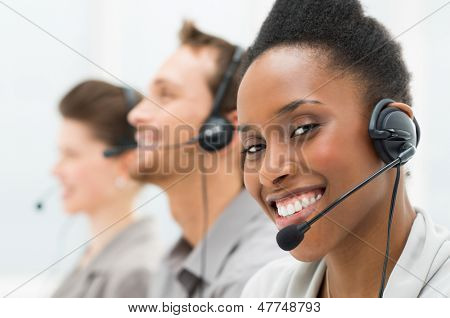 Closeup Of Happy African American Telephone Operator with Her Colleagues