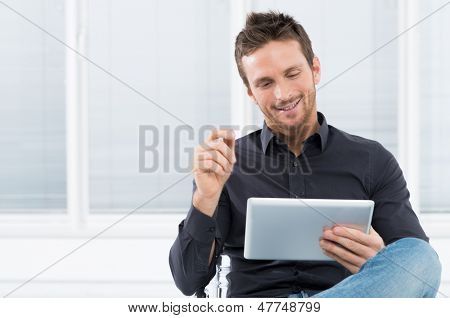 Portrait Of A Handsome Young Happy Man Using Digital Tablet