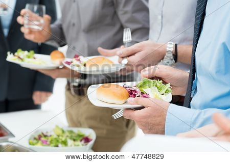 Closeup Of Business People's Hands Having Lunch Together