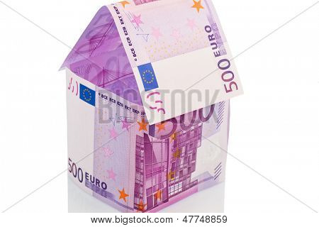 a house built with money euro appear on a white background. building society, building houses and buying a house.