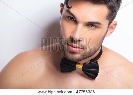 closeup on the face of a serious young topless man wearing a bowtie and looking at the camera. on gray background