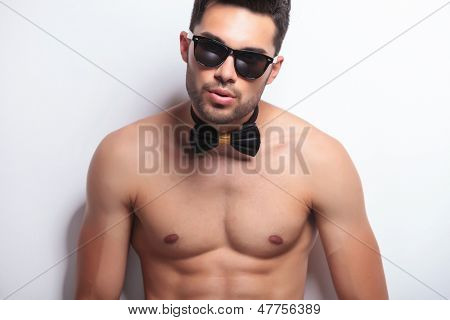 young topless man looking at the camera. on gray background