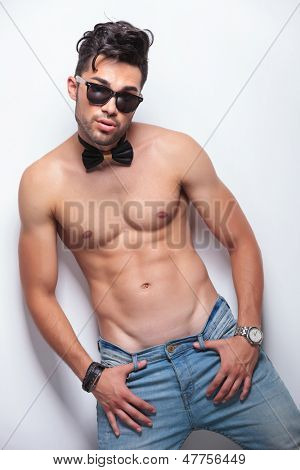 young topless man holding both thumbs in the loops of his jeans while looking at the camera . on gray background