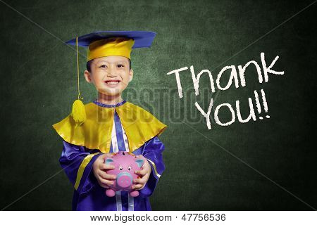 Cheerful Boy In Scholar Gown Holding Piggybank At Class