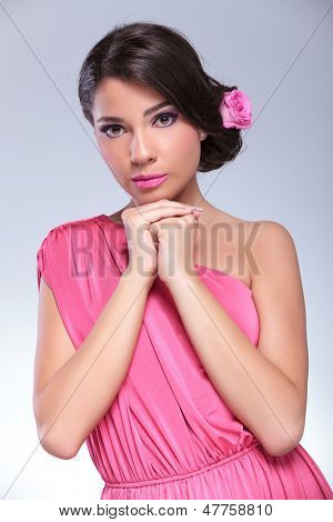 young beauty woman with hands together looking at the camera. on a light gray background