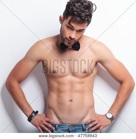 waist up portrait of a young topless man standing with his hands on his hips and looking at the camera. on gray background
