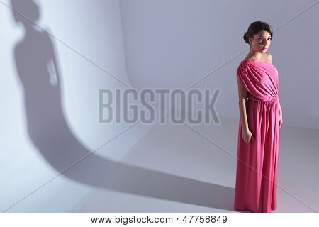 high angle full length photo of a young beauty woman looking up at the camera. on a light gray background with shadow