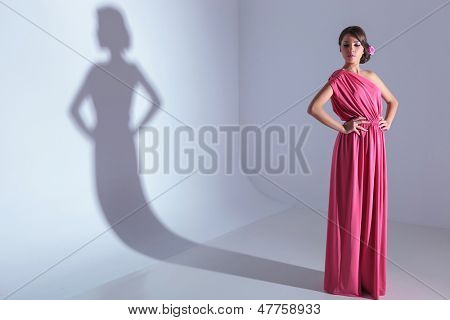 full length photo of a classy young beauty woman looking down while with hands on hips. on a light gray background