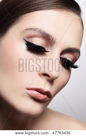 Close-up portrait of young beautiful woman with eyeliner and fake eyelashes