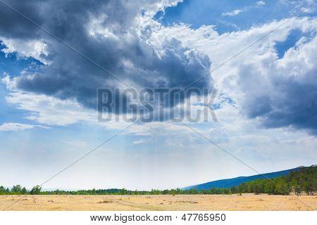 Beautiful clouds in blue sky over field steppe landscape horizon in Siberia.