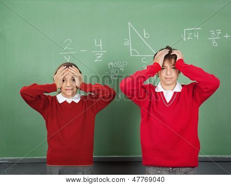 Portrait of confused teenage students standing against board in classroom