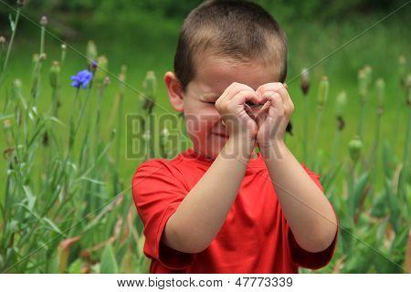 Cute little boy making heart with hands