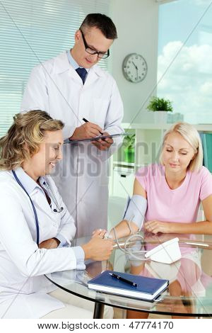 Vertical image of a nurse measuring blood pressure while male doctor diagnosing