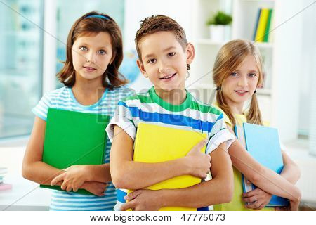 Portrait of three adorable kids holding textbooks