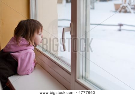 Girl And Winter Behind Window.