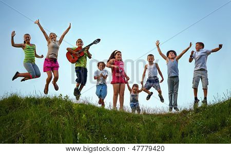 Happy Kids Jumping On Summer Field