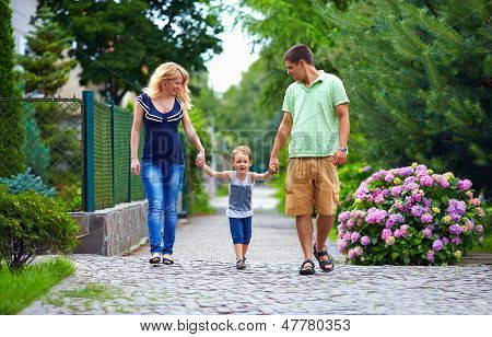 Happy Family Of Three Persons Walking The Street