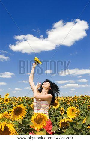 Mujer divertida en el campo de girasoles