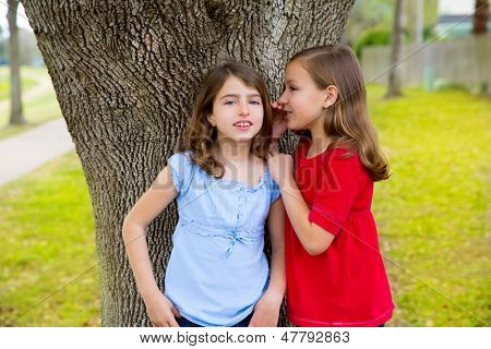 children kid friend girls whispering ear playing smiling in a park tree outdoor