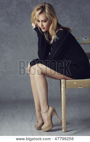 Beautiful blond woman with long legs wearing black cardigan, beige high heels on grunge studio background sitting on a rustic chair
