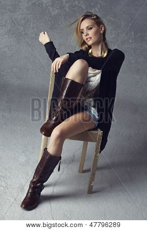 Beautiful blond woman wearing black cardigan, jean shorts and leather boots on grunge studio background sitting on a rustic chair
