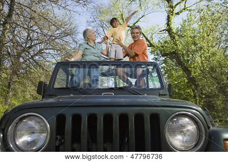 Grandparents and grandson standing in jeep