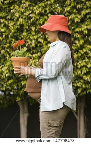 Pregnant woman holding potted plant