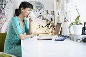 foto of side view people  - Side view of young businesswoman drinking coffee at office desk - JPG